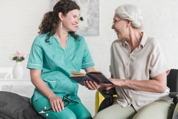 Senior woman holding book sitting on wheelchair making fun with beautiful nurse Free Photo
