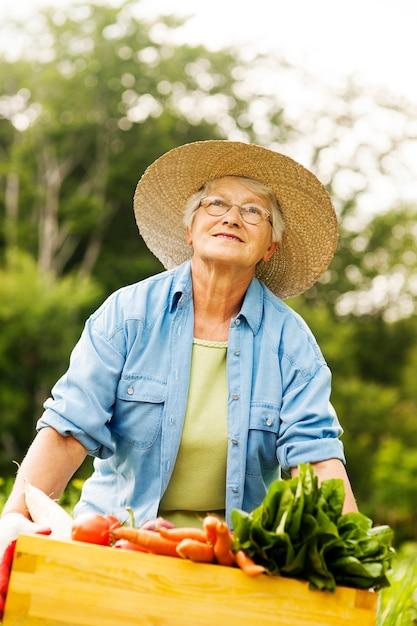 Casella senior della holding della donna con le verdure Foto Gratuite