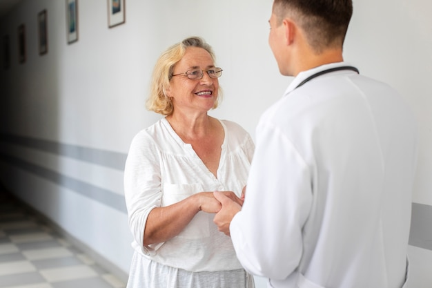 Senior woman holding doctor hands Free Photo