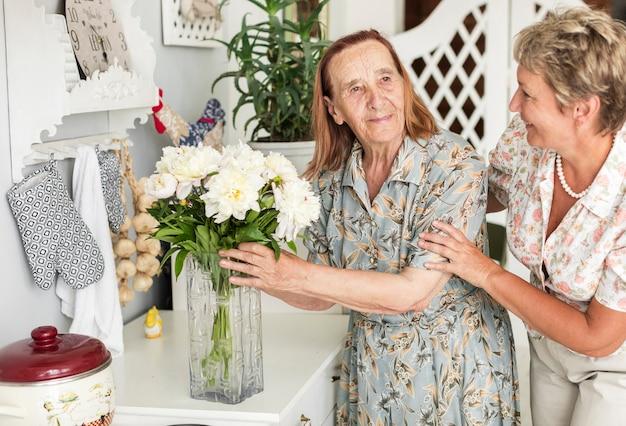 Senior woman holding white flower vase standing near her daughter Free Photo