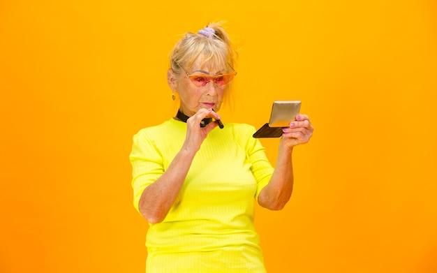 Старшая женщина в ультрамодной одежде изолирована на ярко-оранжевом Бесплатные Фотографии
