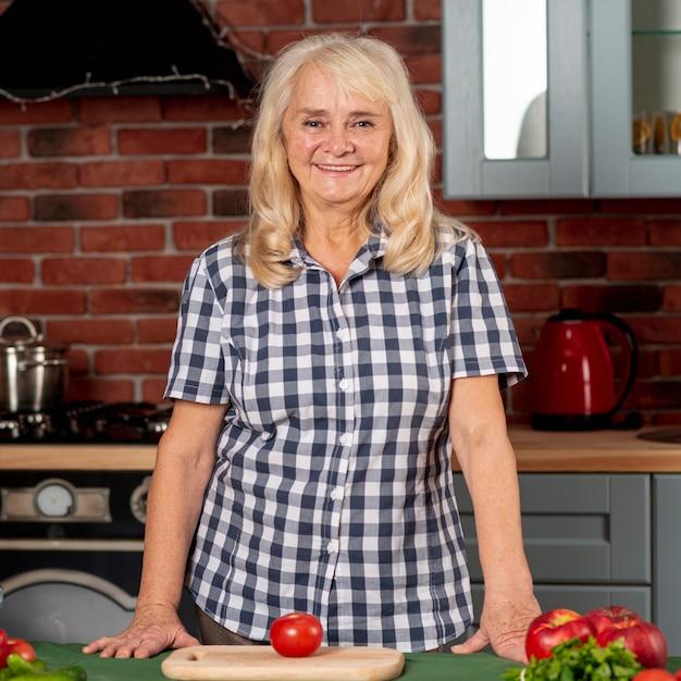 Senior woman in kitchen prepared to cook Free Photo