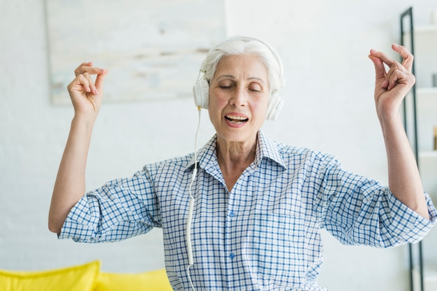 Senior woman listening music on headphone snapping her fingers Free Photo
