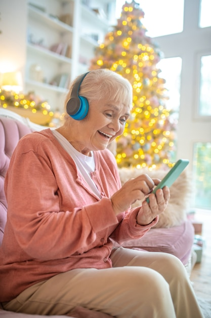 Senior woman listening to music in headphones Premium Photo