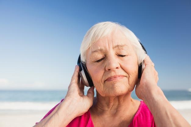 Senior woman listening music with headphone Premium Photo
