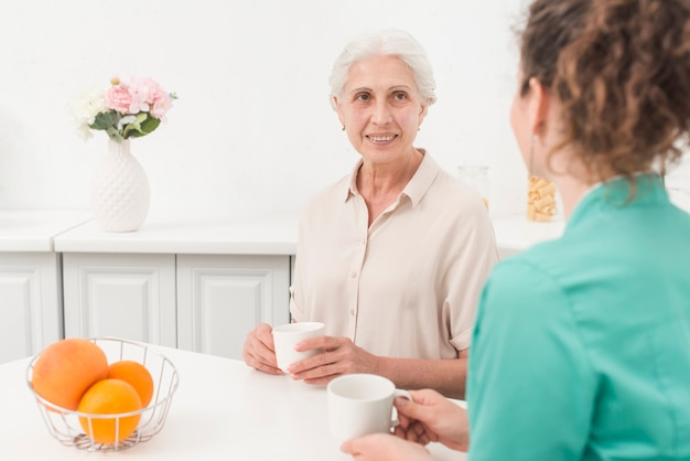 Senior woman looking at female nurse while drinking coffee Free Photo