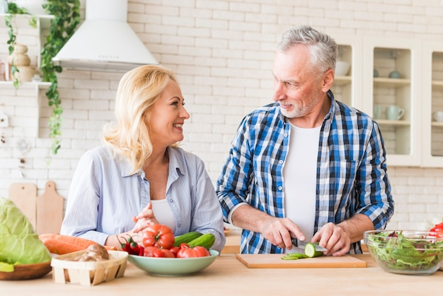 Senior woman looking at her husband cutting the slice of cucumber with knife Free Photo