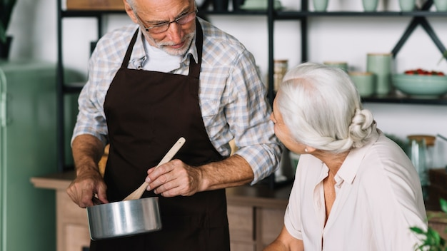 Senior woman looking at man preparing food in the kitchen Free Photo