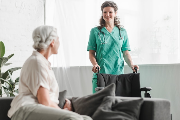 Senior woman looking at smiling female nurse with wheelchair Free Photo