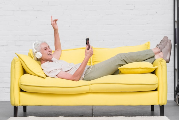 Senior woman lying on yellow sofa enjoying the music on mobile through headphone Free Photo