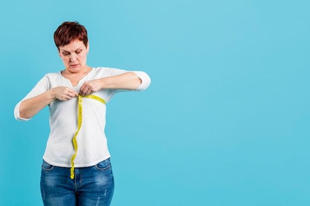 Senior woman measuring chest Free Photo