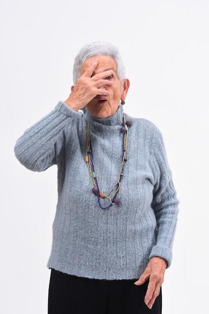 年配の女性が白い背景の上の顔に手を覗く Premium写真