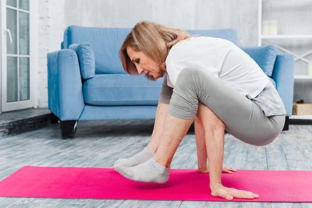 Senior woman practicing yoga at home Free Photo