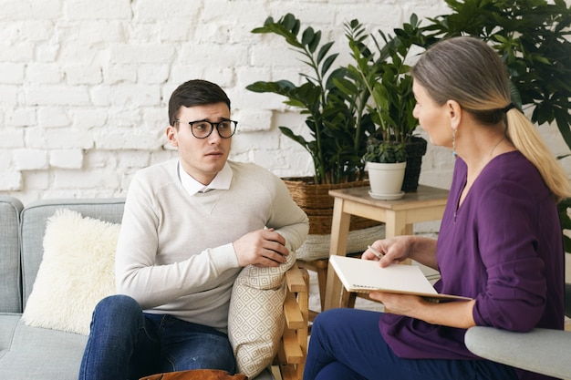 Senior woman psychotherapist or counselor writing something down in notebook during therapy session with frustrated depressed young male in spectacles. psychology, counseling and mental health Free Photo