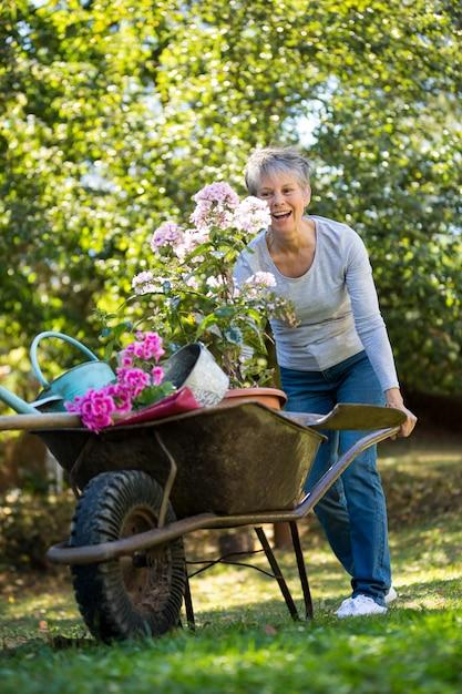 Senior woman pushing wheelbarrow in garden | Premium Photo