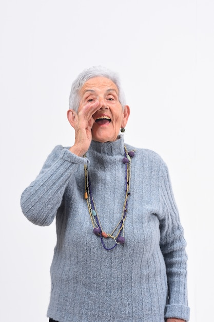 Senior woman putting a hand in labo and is screaming on white background Premium Photo