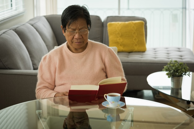 Senior woman reading book at table Premium Photo