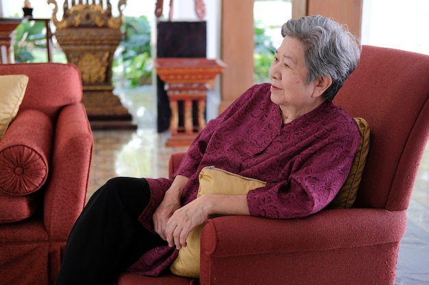 Senior woman resting relaxing on sofa couch in living room Premium Photo