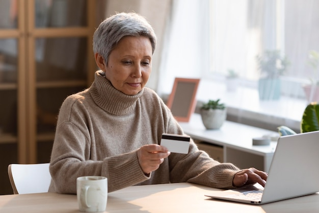 Старшая женщина, делающая покупки в интернете Бесплатные Фотографии