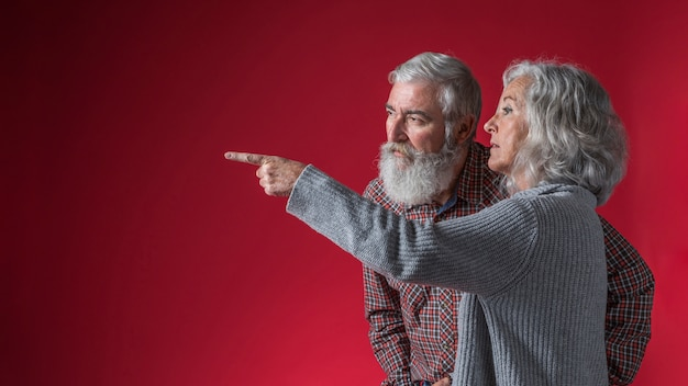 Senior woman showing something to her husband by pointing finger against red background Free Photo