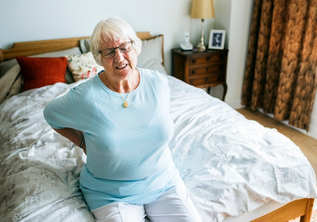 Senior woman sitting on the bed in pain Premium Photo