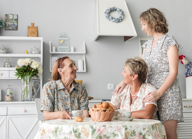 Senior woman sitting on chair looking at her daughter and grand daughter in kitchen Free Photo