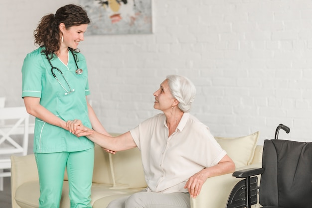 Senior woman sitting on sofa holding nurse's hand Free Photo
