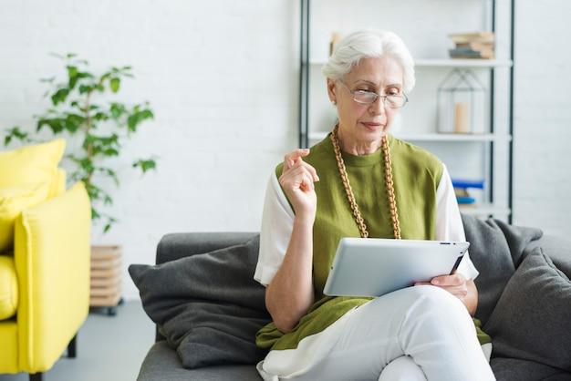 Senior woman sitting on sofa looking at digital tablet Free Photo