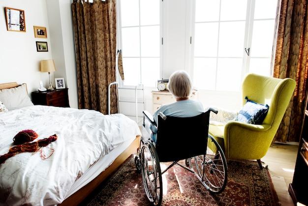 Senior woman sitting on the wheelchair alone Premium Photo