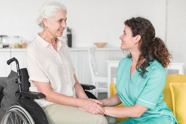 Senior woman sitting on wheelchair holding nurse's hand Free Photo