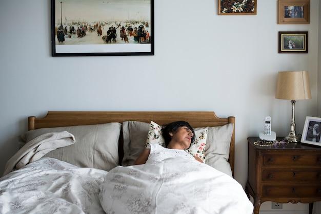 Senior woman sleeping alone on the bed Premium Photo