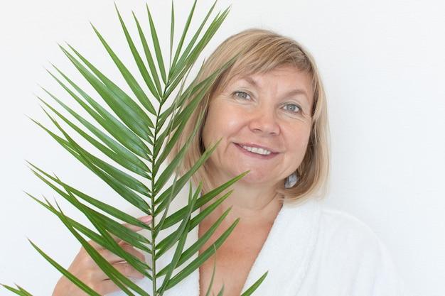 Старшая женщина улыбается anti-age концепция с пальмовых листьев. лицо зрелой женщины после санаторно-курортного лечения. старость в радость, клиника пластической хирургии, бабушка милашка, косметология, новый пенсионер, пенсионер, зрелые люди Premium Фотографии