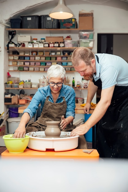 Senior woman spinning clay on a wheel with teacher at pottery class Premium Photo
