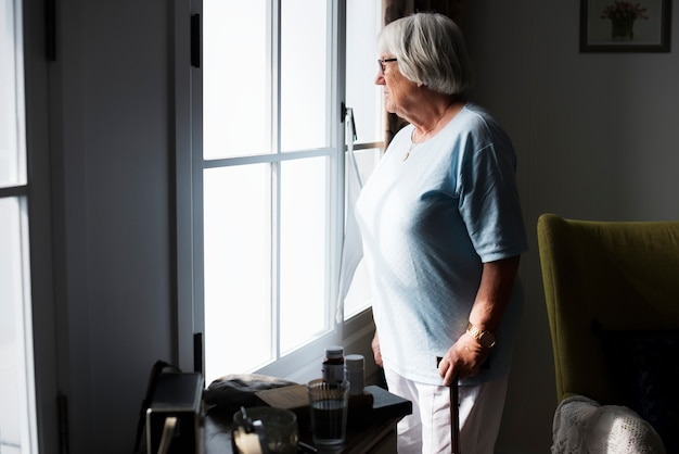 Senior woman standing alone at home Free Photo