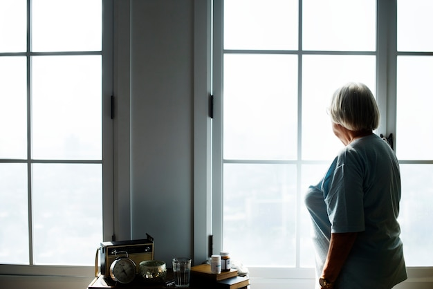 Senior woman standing alone at home Premium Photo