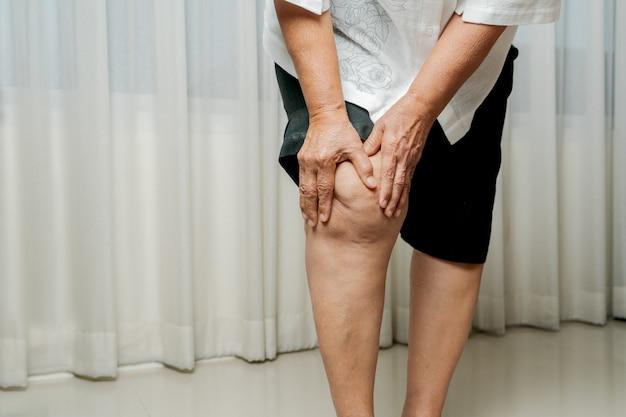 Старшая женщина страдает от боли в колене дома, концепция проблемы со здоровьем Premium Фотографии