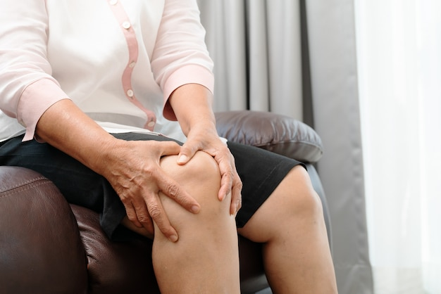 Senior woman suffering from knee pain at home Premium Photo