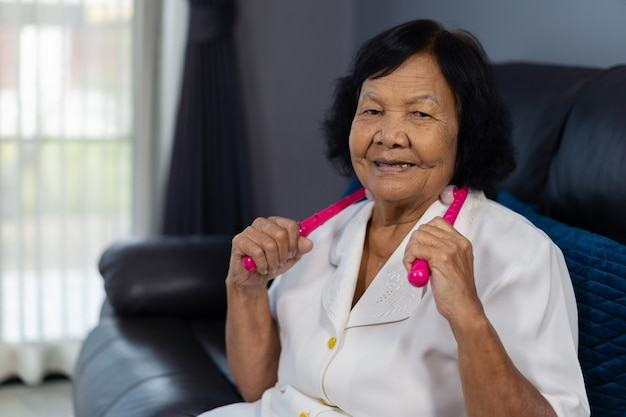 Senior woman suffering from neck pain and massaging by massage assistant tools Premium Photo