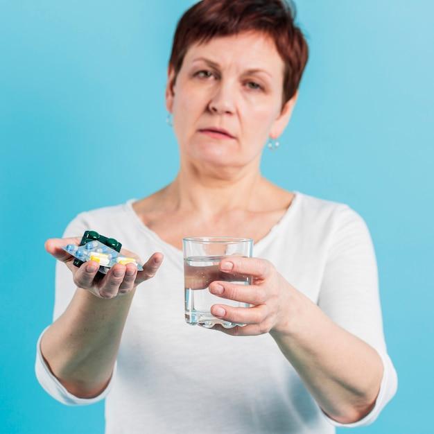 年配の女性が薬を服用 無料写真