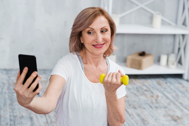 Senior woman taking selfie with dumbbells in hand Free Photo