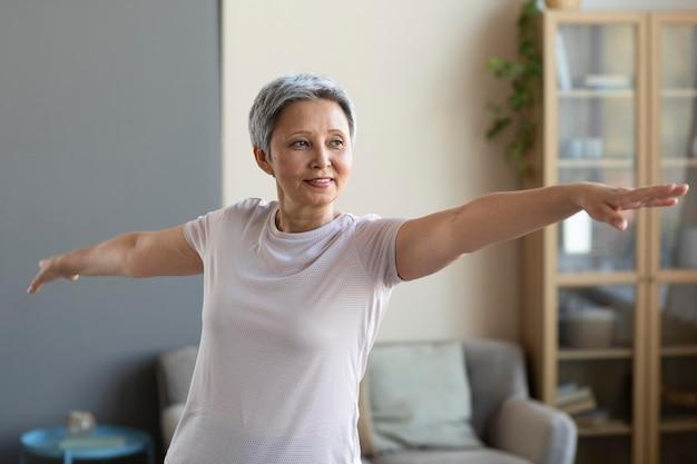 Старшая женщина тренируется дома Premium Фотографии