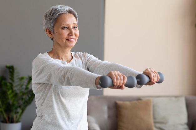 自宅でトレーニングする年配の女性 無料写真