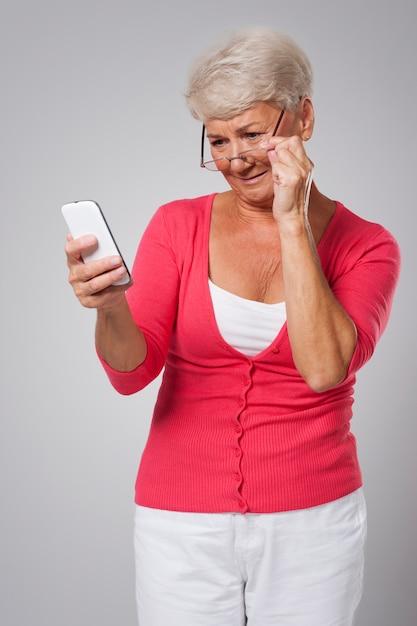 現代の携帯電話を使おうとしている年配の女性 無料写真