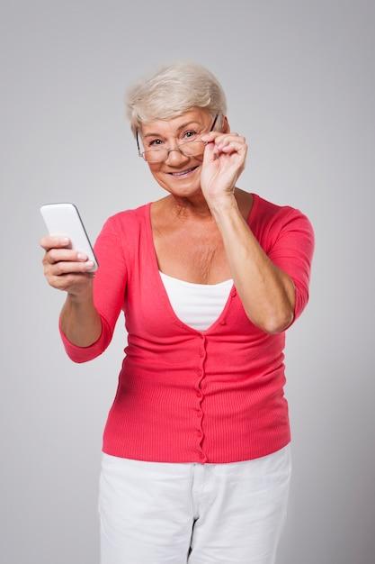 現代のスマートフォンを使用して年配の女性 無料写真