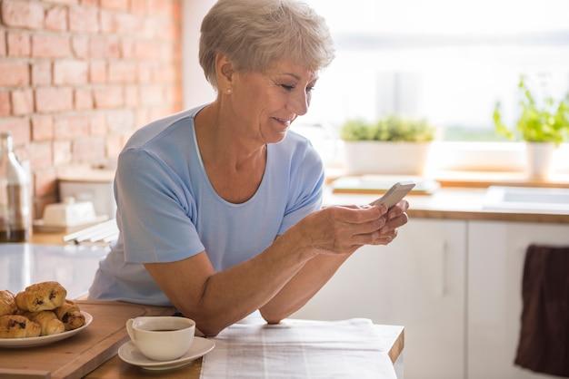 携帯電話を使っている年配の女性 無料写真