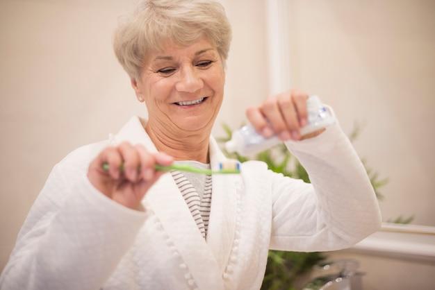 Senior donna usando il suo spazzolino da denti Foto Gratuite