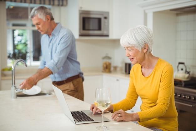 キッチンでラップトップを使用して年配の女性 Premium写真