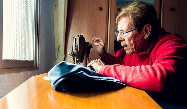 Senior woman using sewing machine concentrated with natural light coming through the window Premium Photo