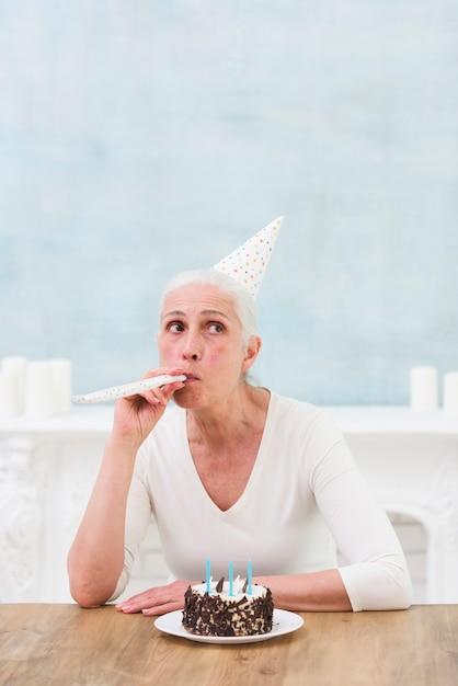 Рог партии шляпы старшей женщины нося дуя с вкусным тортом и свечами на деревянном столе Бесплатные Фотографии