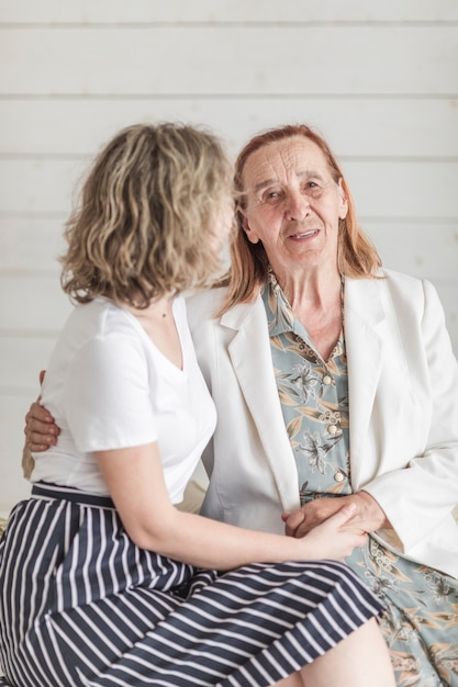 Senior woman with her grand daughter sitting together Free Photo